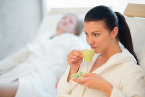 Woman drinking coffee at spa with friend in background