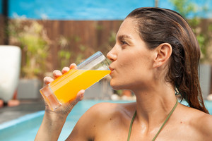 Woman drinking orange juice in the pool