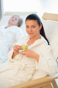 Woman enjoy coffee at beauty spa with friend in background