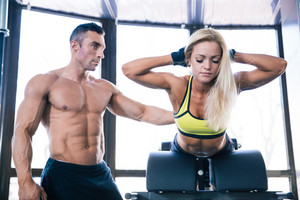 Woman flexing back muscles on bench with coach in gym