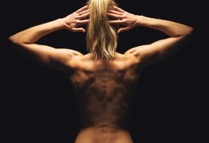Woman flexing her muscles and showing her toned back