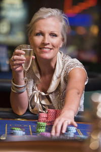Woman gambling at roulette table in casino