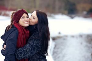 Woman Giving Her Friend a Friendly Kiss