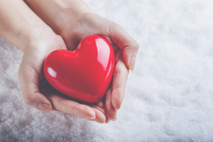 Woman hands are holding a beautiful glossy red heart in a snow winter background. Love and St. Valentine cozy concept.