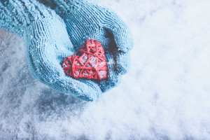 Woman hands in light teal knitted mittens are holding a beautiful a entwined vintage romantic red heart in a snow background.