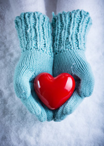 Woman hands in light teal knitted mittens are holding a beautiful glossy red heart in a snow background.