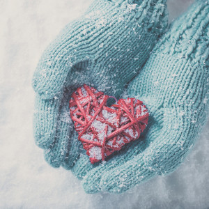Woman hands in light teal knitted mittens are holding a beautiful glossy red heart in a snow winter background.