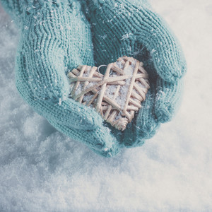 Woman hands in light teal knitted mittens are holding a beautiful heart in a snow background.  Instagram effect.