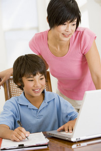 Woman helping young boy with laptop do homework in dining room smiling