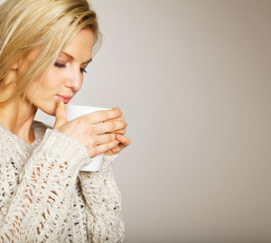 Woman holding a cup of coffee and enjoying the smell of its aroma