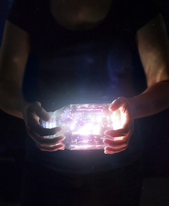 Woman holding a jar with bright glowing lights and colors.