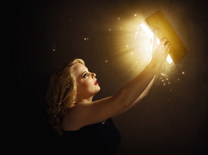 Woman holding a magic book with lights.