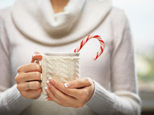 Woman holds a winter cup close up. Woman hands with elegant french manicure nails design holding a cozy knitted mug with cocoa