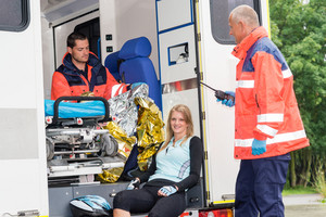 Woman in ambulance with emergency paramedics aid bike accident smiling