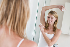 Woman in bathroom applying deodorant smiling