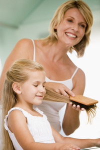 Woman in bathroom brushing young girl's hair