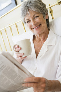 Woman in bedroom with coffee and newspaper smiling
