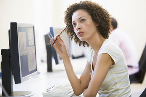 Woman in computer room thinking