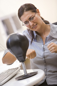 Woman in computer room using small punching bag for stress relief