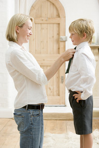Woman in front hallway fixing young boy's tie and smiling