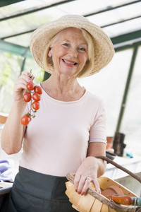 Woman in greenhouse holding cherry tomatoes smiling