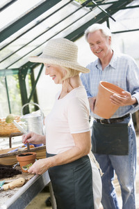 Woman in greenhouse planting seeds and man holding pot smiling