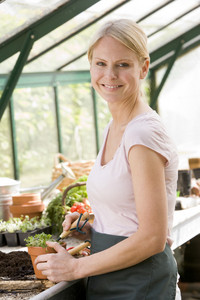 Woman in greenhouse raking soil in pot smiling
