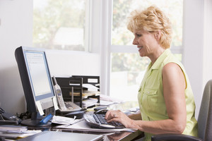 Woman in home office at computer smiling