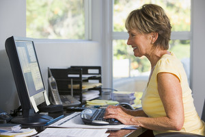 Woman in home office using computer smiling