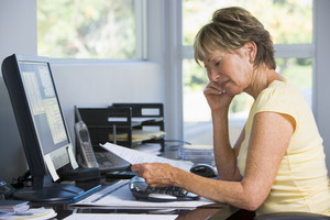 Woman in home office with computer and paperwork