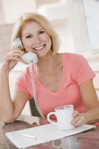 Woman in kitchen using telephone and smiling