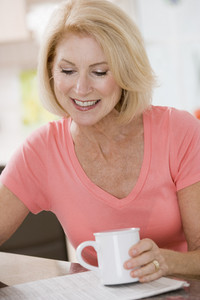 Woman in kitchen with coffee and newspaper smiling