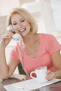 Woman in kitchen with coffee using telephone smiling