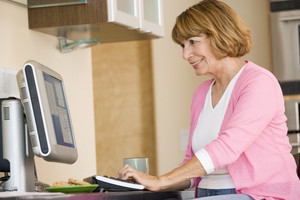 Woman in kitchen with computer and coffee smiling