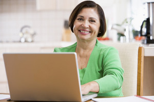 Woman in kitchen with laptop smiling