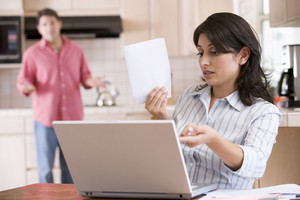 Woman in kitchen with paperwork using laptop with man in background