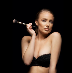 Woman in lingerie holding a makeup brush like a cigaret. Beautiful lady with perfect soft skin and make up.
