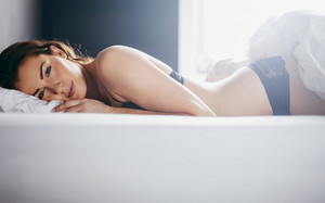 Woman in lingerie lying in her bed looking at camera. Beautiful young woman relaxing in bedroom.