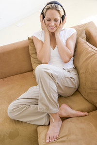 Woman in living room listening to headphones smiling