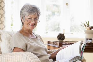Woman in living room reading book smiling