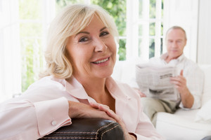 Woman in living room smiling with man in background reading newspaper