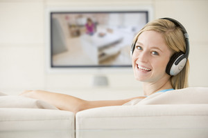 Woman in living room watching television and wearing headphones smiling