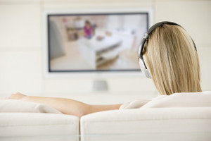 Woman in living room watching television and wearing headphones