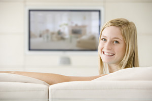 Woman in living room watching television smiling