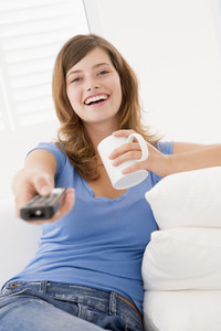 Woman in living room with remote control and coffee smiling