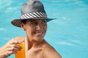 Woman in the edge of the pool drinking juice