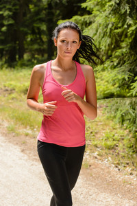 Woman jogging outdoor running on sunny day countryside path