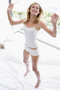 Woman jumping on bed smiling