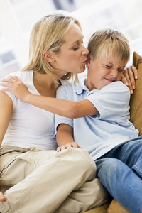 Woman kissing disgusted young boy in living room