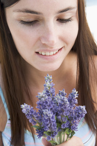 Woman looking at bunch of wild flowers